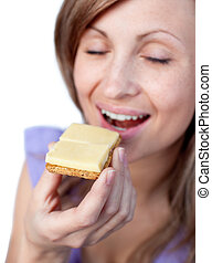 Young woman eating a cracker with cheese isolated on a white...