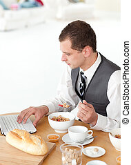 Young businessman using a laptop while having breakfast