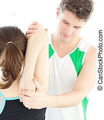 Young physical therapist checking a womans shoulder during a...