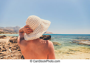 woman with straw hat protects from sun on the beach