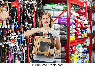 Happy Woman Holding Pet Carrier In Store - Portrait of happy...