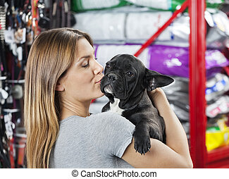 Woman Kissing French Bulldog At Store - Loving mid adult...