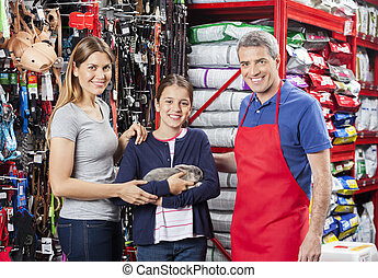 Girl Holding Rabbit With Mother And Salesman In Store -...