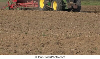 tractor cultivating and sowing cereal field in early autumn...