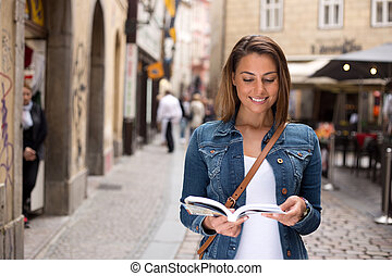 tourist with guidebook - young tourist reading her guide...