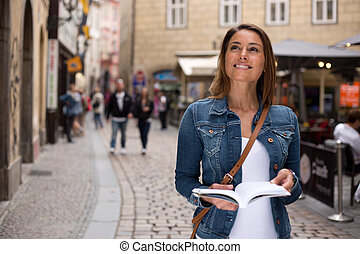 tourist with guidebook - a young tourist sightseeing holding...