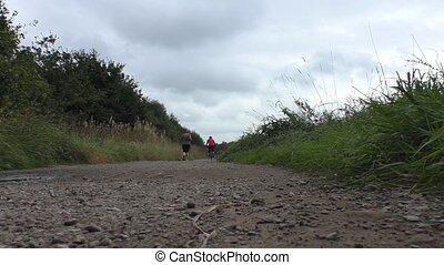 Obese woman jogging - Overweight woman jogging outdoors, man...