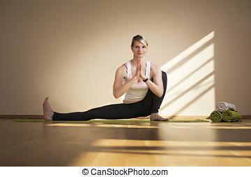 Frau die Yoga macht auf einer Yogamatte