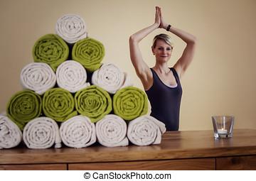 Frau die Yoga macht mit Vordergrund kasten und matten und...