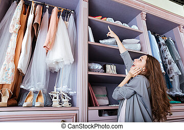 Young woman choosing what to wear in a closet - Young...