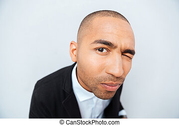 Funny african man closed one eye and looking at camera -...