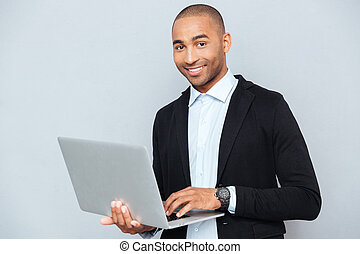 Happy african american young man holding and using laptop