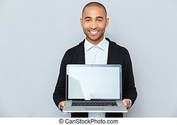 Smiling african american young man holding blank screen...