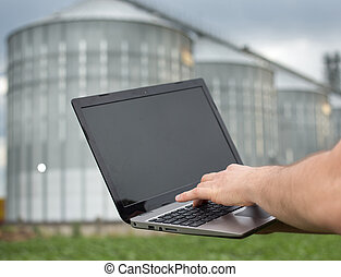 Man holding laptop in front of grain silo - Close up of...