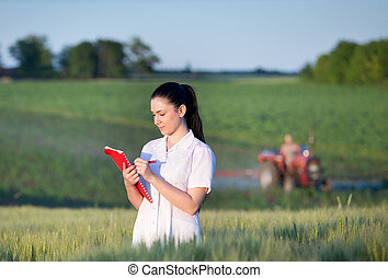 Agronomist standing in wheat field - Young pretty agronomist...