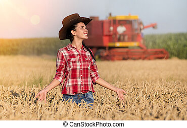 Farmer girl and combine harvester in wheat field