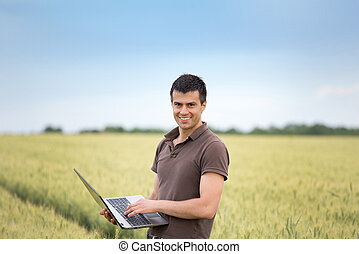 farmer with laptop in wheat field - Young attractive farmer...