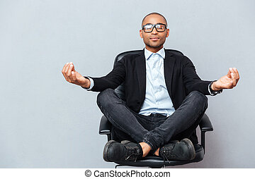 Attractive young man in glasses meditating on office chair -...