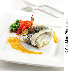Sea bass fillet on a plate with sauce, peppers and green...