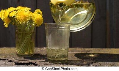 Pouring dandelion tea into a glass - Pouring dandelion tea...