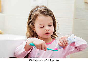Little girl in bathroom putting a toothpaste on toothbrush -...