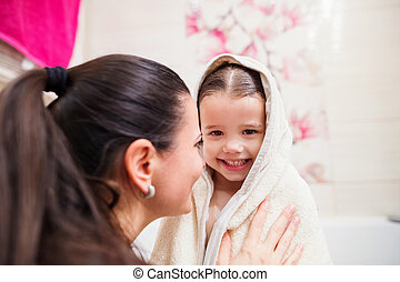 Mother drying daughter after taking bath, wrapped in towel -...