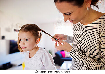 Mother braiding hair of her daughter in the morning -...