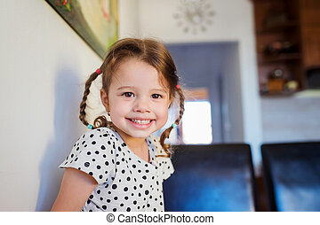 Little girl with two braids in dotted t-shirt smiling - Cute...