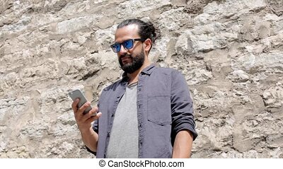 man texting message on smartphone at stone wall 4 - leisure,...