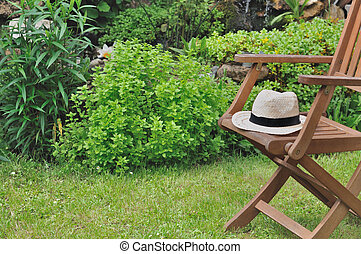 break in garden - straw hat in a wooden chair in a greenery...