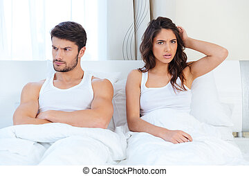 Unhappy separate couple lying in a bed
