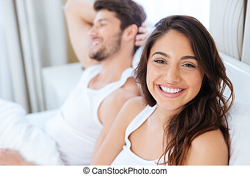 Smiling relaxed young couple lying together