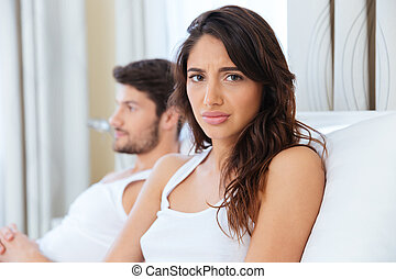 Unhappy woman in bed with man on the back - Unhappy upset...