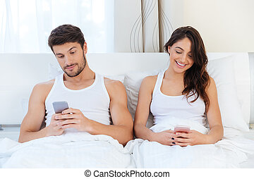 Happy couple in a bed with mobile phones - Young happy...