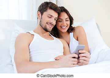 Young sweet couple in bed looking at a mobile phone
