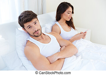 Husband while his internet addict wife is using mobile phone