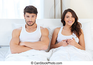 Angry young man lying on the bed with a woman at home