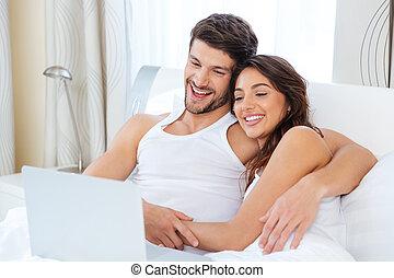 coppia, letto, loro,  computer, casa, usando, dire bugie