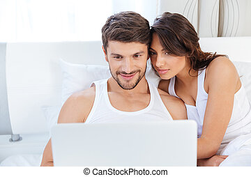 Beautiful young couple looking at laptop in bed - Happy...