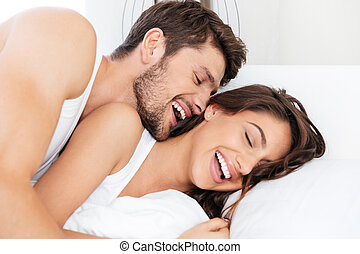 Happy couple laughing in the bed - Happy beautiful young...