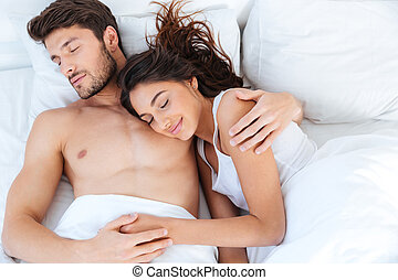 Lovely couple sleeping on their bed at home