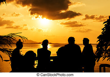 Silhouette of people at bar sunset background