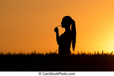 Silhouette of woman lighting cigarette - Silhouette of young...