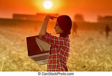 Woman with laptop in the field - Young woman with laptop...