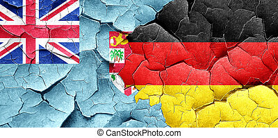 Fiji flag with Germany flag on a grunge cracked wall