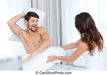 Excited couple pillow fighting at home - Excited young...