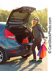 Caucasian woman putting her shopping bags into the car trunk...