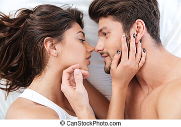 Close-up portrait of a beautiful kissing couple in bed -...