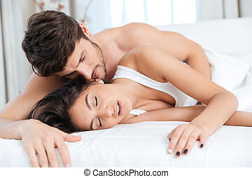 Young couple hugging in the bed in bedroom - Young happy...