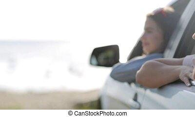 happy teenage girls or women in car at seaside 2 - summer...